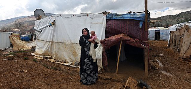 Mervat, 31, stands outside of her tent as she holds her 9-month-old daughter, Shurouk, at a camp for Syrian refugees in Lebanon's Bekaa Valley on Tuesday, March 11, 2014. Credit: AP Photo/Bilal Hussein.