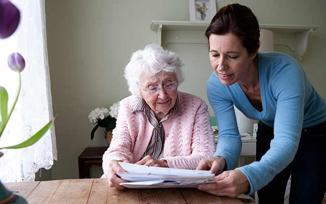 Woman reading to mother at table