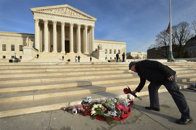James Peck of Springfield, Virginia, lays flowers down at a makeshift memorial for Supreme Court Justice Antonin Scalia on Sunday February 14, 2016, in Washington, D.C. Photo by Matt McClain/ The Washington Post via Getty Images