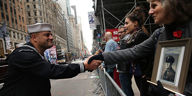 The daughter of World War II veteran Henry Morth shakes the hand of a sailor as she cheers veterans in New York City's Veterans Day Parade on Nov. 11, 2015. (Photo by Spencer Platt/Getty Images)