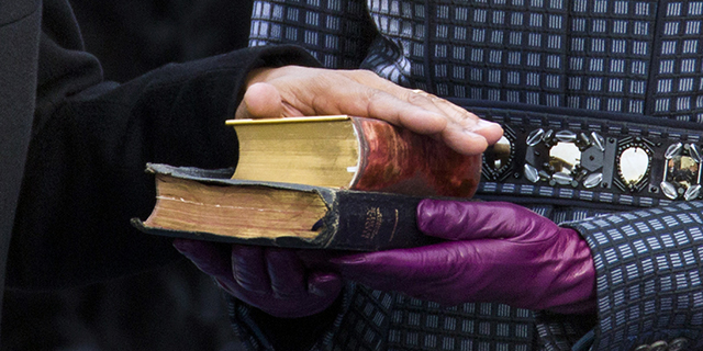 President Obama places his hand on two Bibles held by first lady Michelle Obama as his recites the oath of office during swearing-in ceremonies on the West front of the U.S Capitol in Washington. (Brooks Kraft LLC/Corbis via Getty Images)