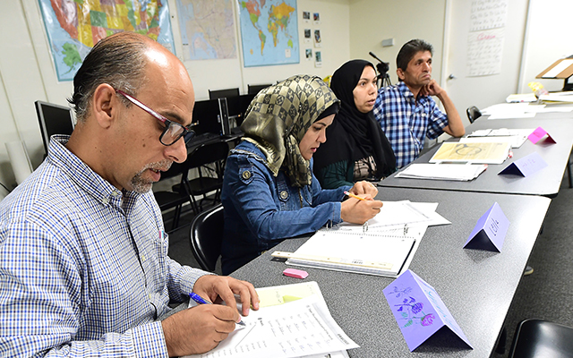 Syrian refugees take notes during their Vocational ESL class at the International Rescue Committee center in San Diego on Aug. 31, 2016. (Frederic J. Brown/AFP/Getty Images)