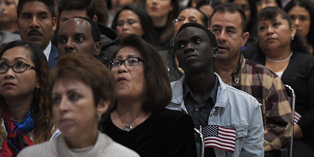 Immigrants listen to a speech as they wait to become U.S. citizens at a naturalization ceremony in Los Angeles. (Mark Ralson/AFP/Getty Images)