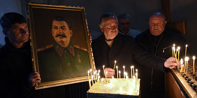 A man holds a portrait of late Soviet dictator Joseph Stalin as others place candles at a church in Stalin's native town of Gori, Georgia, on March 5, 2017, the 64th anniversary of his death. (Vano Shlamov/AFP/Getty Images)