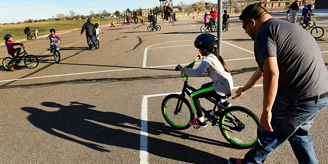 Elsiana Ruiz, 8, gets help learning to ride her bike from her father, Sinahy, at a playground in Aurora, Colorado. (Helen H. Richardson/The Denver Post via Getty Images)