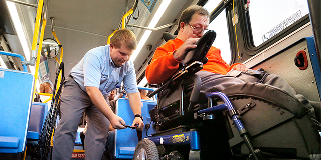 A Metro bus driver fastens a strap to secure a passenger's wheelchair in Portland, Oregon. (Gregory Rec/Portland Press Herald via Getty Images)