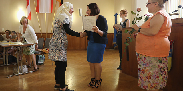 Syrian refugee Marwad Khaled, center left, is awarded a completion certificate for a beginner's level German language class by Dilek Kolat, Berlin state senator for Work, Women and Integration, in Berlin in July 2016. The language program is financed by the city of Berlin to train more than 20,000 of the refugees granted asylum in Germany. (Sean Gallup/Getty Images)