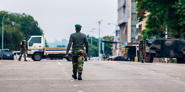 """Zimbabwean soldiers stand at an intersection as they regulate traffic in Harare on Nov. 15, 2017. Generals denied that the military had staged a coup but vowed on state television to target """"criminals"""" close to President Robert Mugabe. (AFP/Getty Images)"""