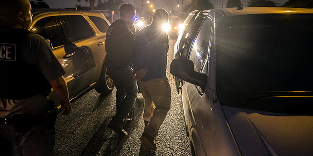 Immigration and Customs Enforcement agents take a man into custody in Downey, California, in April 2017. (Brian van der Brug/Los Angeles Times via Getty Images)