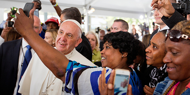 Cartrice Haynesworth, center, has a selfie taken with Pope Francis as he visits Catholic Charities of the Archdiocese of Washington in September 2015 in Washington, D.C. (David Goldman-Pool/Getty Images)