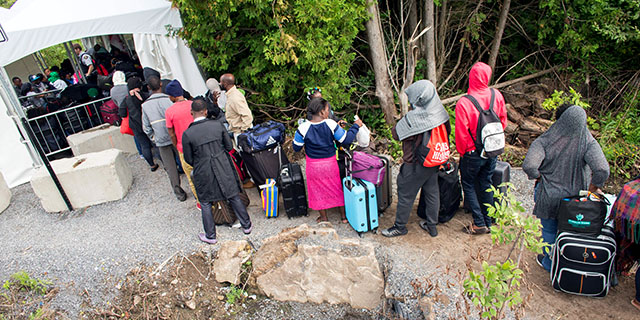 Asylum seekers wait to cross the border into Canada near Champlain, New York, in August 2017. (Geoff Robins/AFP/Getty Images)