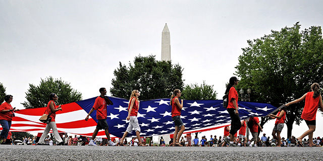 Volunteers carry an American flag down Constitution Avenue during the National Independence Day Parade in Washington, D.C. (Bill O'Leary/The Washington Post via Getty Images)