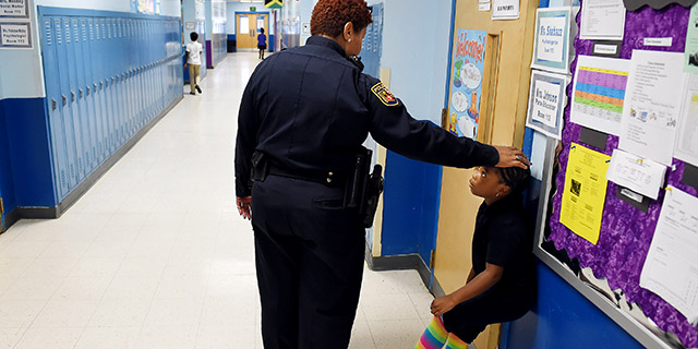 Tiffany Wiggins, a school police officer in Baltimore, talks with a student at Thomas Jefferson Elementary/Middle School in 2015. (Matt McClain/The Washington Post via Getty Images)