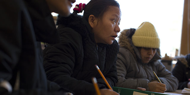 Tika Gurung takes notes during an English class in Burlington, Vermont. Her extended family was resettled in the area, as were hundreds of other refugees from Bhutan and Nepal in recent years. (Robert Nickelsberg/Getty Images)