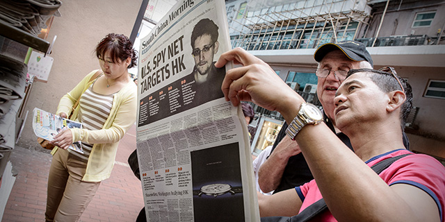 When National Security Agency contractor Edward Snowden released classified documents detailing U.S. government interception of phone calls and electronic communications, it made headlines around the world. Here, two men in Hong Kong read a newspaper in June 2013. (Philippe Lopez/AFP/Getty Images)