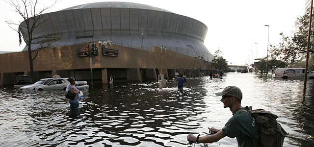 A man pushes his bicycle through flood waters near the Superdome in New Orleans on Aug. 31, 2005. Photo credit: AP Photo/Eric Gay.
