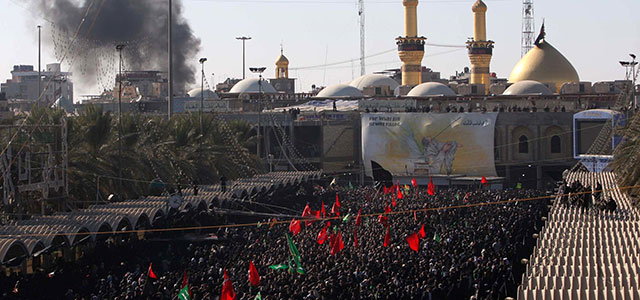 Smoke billows as part of Ashura rituals as Muslim Shia pilgrims gather in the Iraqi holy city of Karbala on December 6, 2011. (Credit: MOHAMMED SAWAF/AFP/Getty Images)