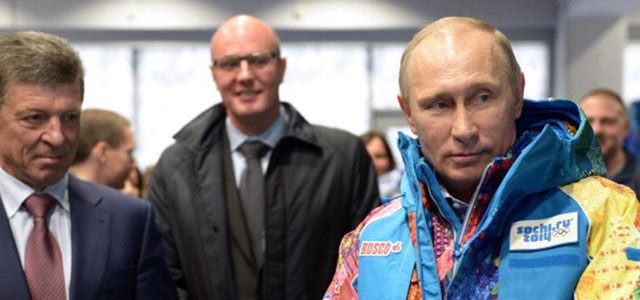Russian President Vladimir Putin (R) tries an Olympic volunteers uniform, visiting an equipment centre in Sochi on January 4, 2014. Credit: ALEXEY NIKOLSKY/AFP/Getty Images