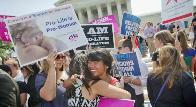 Demonstrators embrace as they react to hearing the Supreme Court's decision on the Hobby Lobby case outside the Supreme Court in Washington.