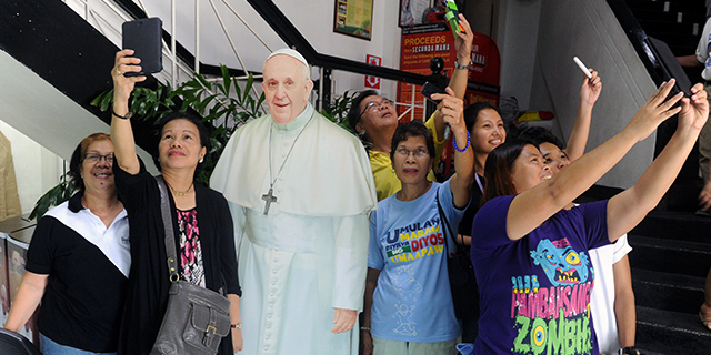 Catholic faithfuls in pose in front of a cardboard stand-up photograph of Pope Francis in suburban Manila, 2014. AFP/Getty Images