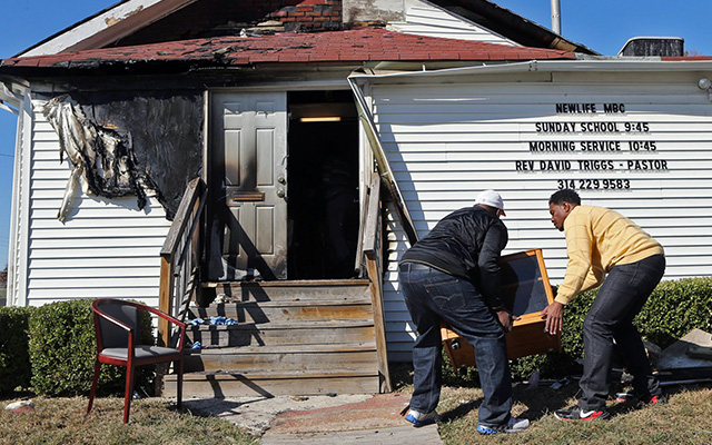 Deacon Clinton McMiller (left) and Pastor David Triggs carry a cabinet back into New Life Missionary Baptist Church in St. Louis on Oct. 18. An outdoor service had been held there because of a fire at the church that was believed to be intentionally set. (J.B. Forbes/St. Louis Post-Dispatch via AP)