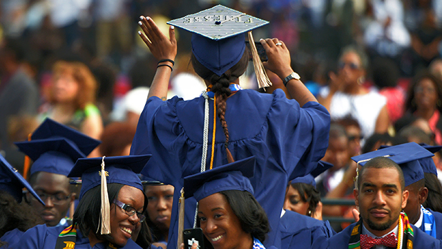 A graduate waves to family members as she takes her seat for Howard University's commencement in May 2014. (Bill O'Leary/The Washington Post via Getty Images)